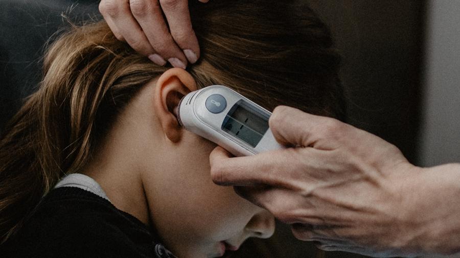 girl getting temperature taken