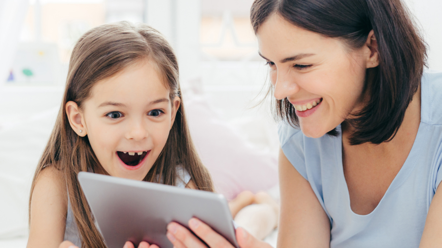 Beautiful mother and daughter watch something funny on tablet computer, connected to wireless internet, spend free time in bedroom, have surprised happy expression. People and leisure concept