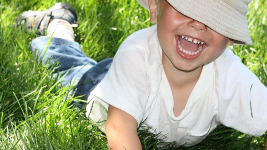 Laughing boy lying on green grass