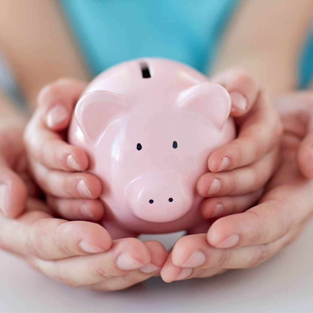 Child and adult holding piggy bank